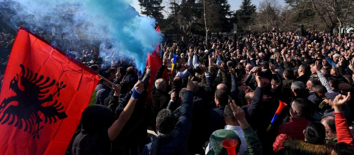 """Albanian opposition supporters gather during a protest outside the Albanian parliament, demanding the resignation of the prime minister, on February 21, 2019, in Tirana. - Thousands rallied in Tirana against Albania's Prime Minister Edi Rama, as the EU condemned opposition mass resignations over alleged corruption by the premier. A heavy police presence was deployed around the parliament in Tirana after a similar opposition rally over the weekend had turned violent. The protesters, who accuse Rama of corruption, lit flares and shouted """"Rama go away!"""" during Thursday's march, but no violence was reported by journalists on the ground. (Photo by Gent SHKULLAKU / AFP)"""